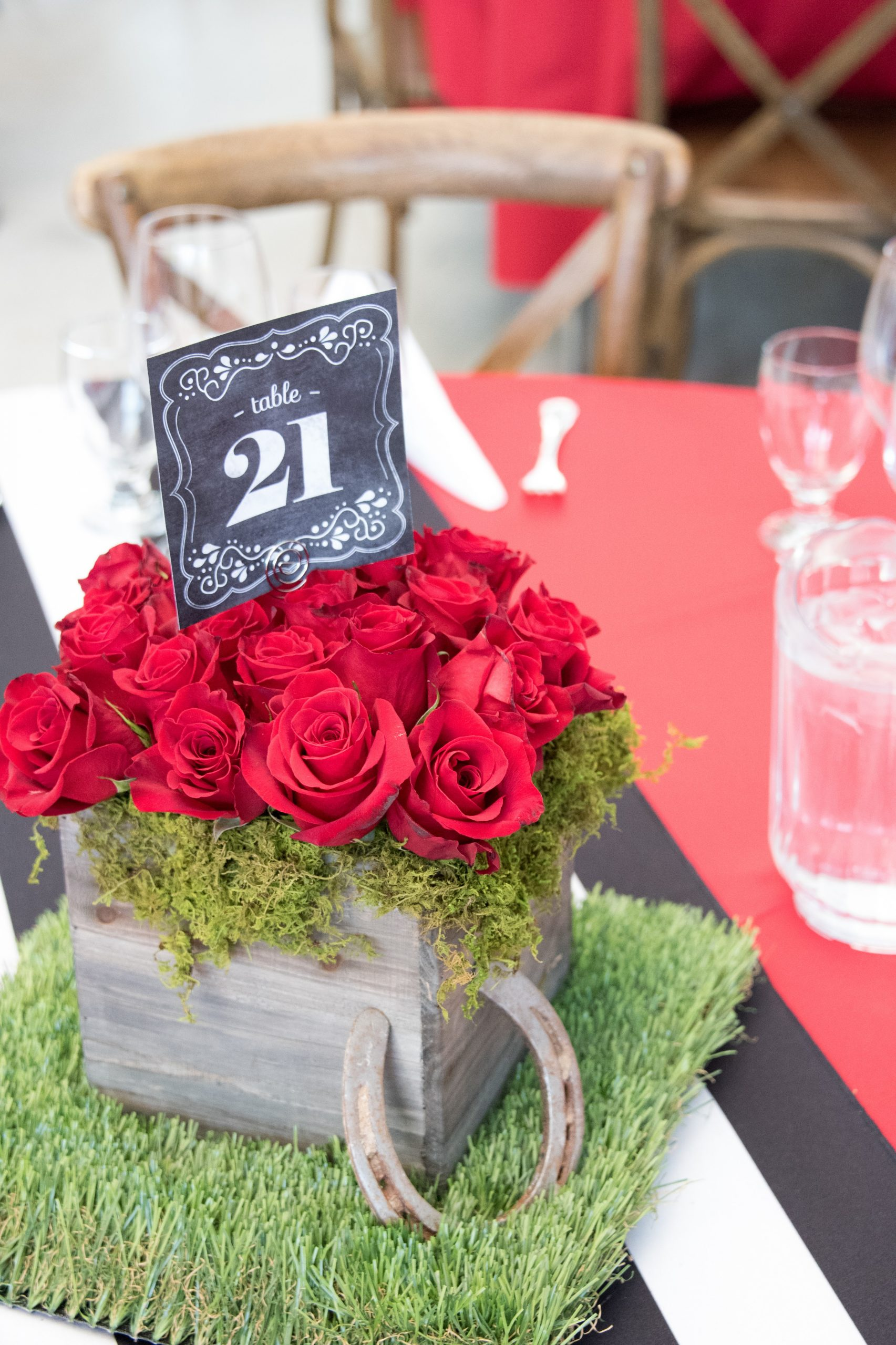 Photo of wooden box container on top of a patch of grass with red roses and the number 21