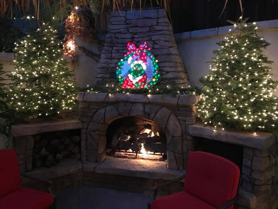 Photo of a fireplace with a lit up wreath hanging over it, surrounded by christmas trees with white lights at Gilroy Foundation's 2017 Holiday Party