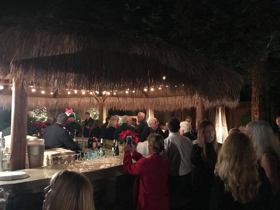 Photo of the tiki bar with guests enjoying the Holiday Party