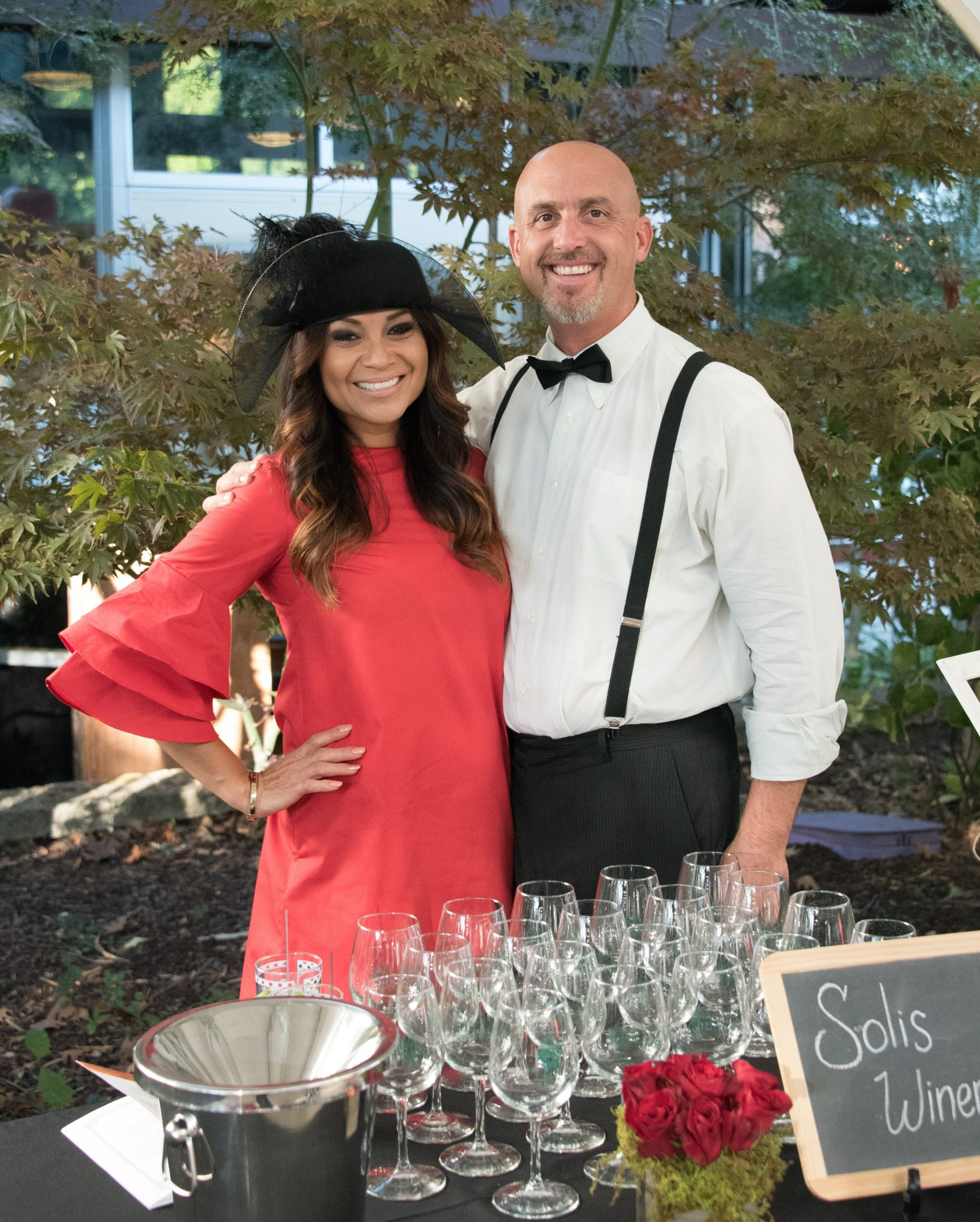Photo of a couple in front of their wine tasting booth at