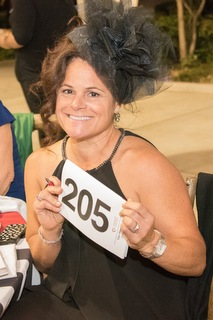 Picture of Jeanie Rizzuto holding up bidder paddle 205 at