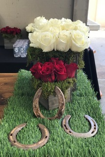 Photo of a flower arrangement in a wooden container sitting on top of grass with 3 horseshoes surrounding centerpiece at