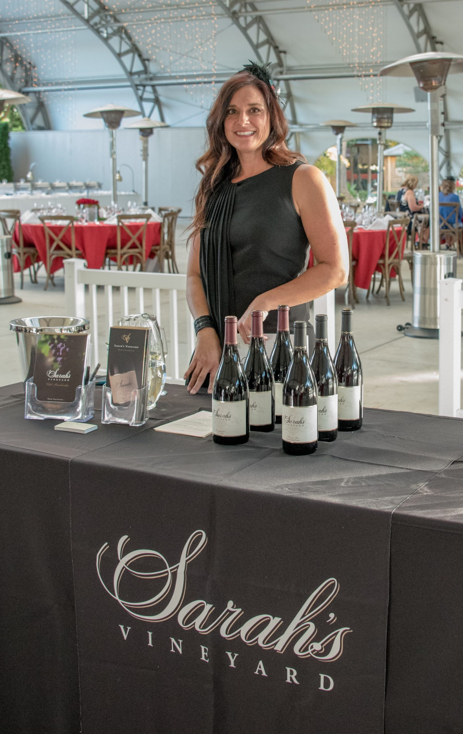 Photo of Stacy Romero-Garcia behind the Sarah's Vineyard wine tasting table at