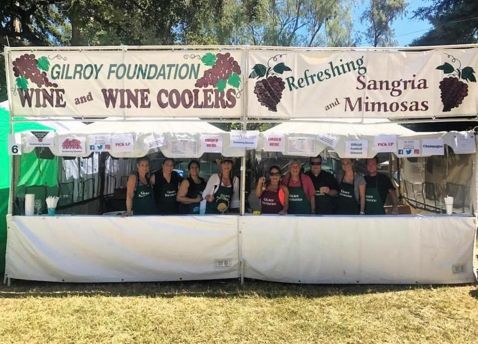 Photo of Gilroy Foundation Wine Cooler Booth at the Garlic Festival with all of the volunteers posing inside for the camera