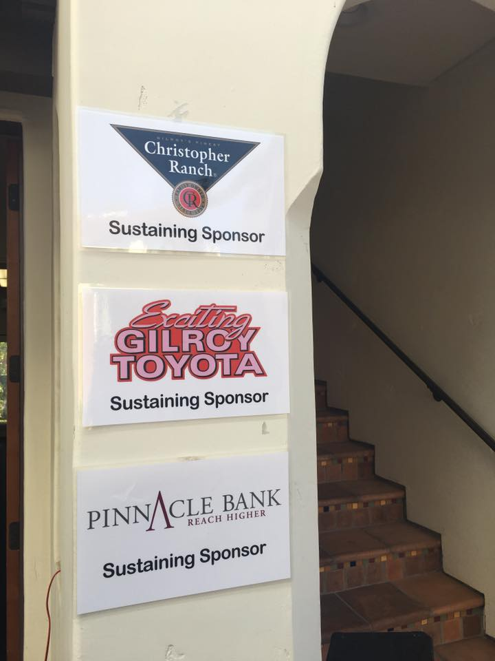 Photo of Gilroy Foundation's Sustaining Sponsor signs, Christopher Ranch, Gilroy Toyota and Pinnacle Bank at Gilroy Foundation Chamber Mixer