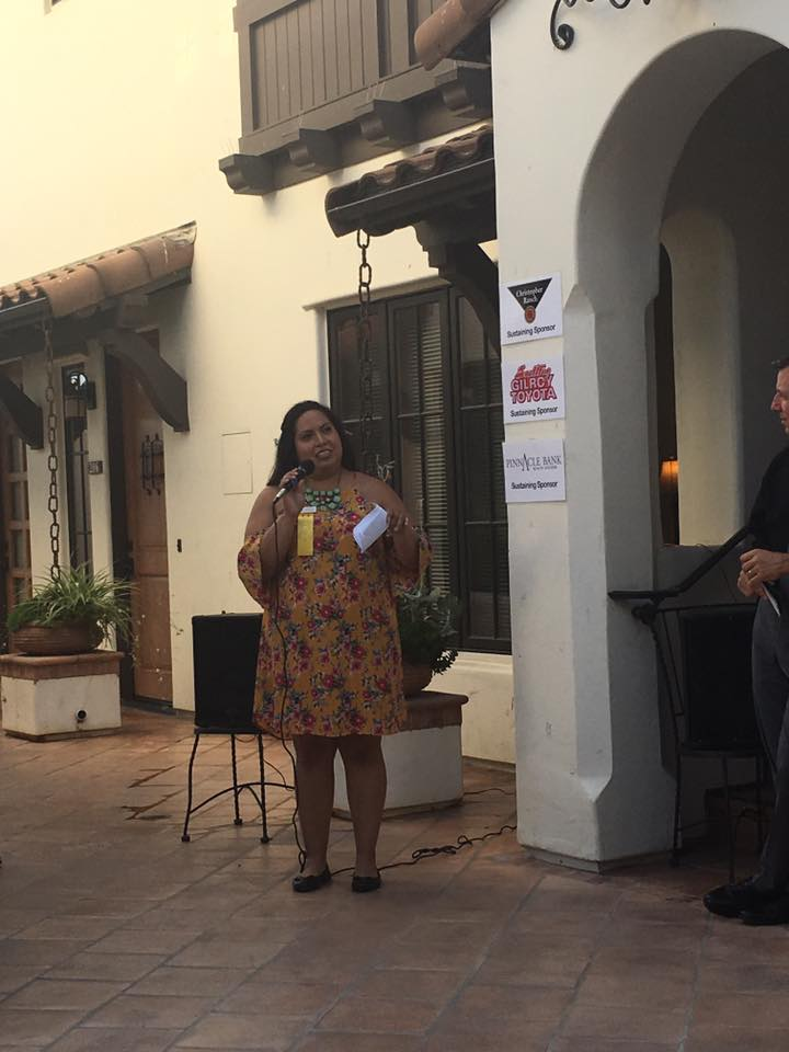 Photo of Yesenia Gonzalez speaking into a microphone at Gilroy Foundation Chamber Mixer