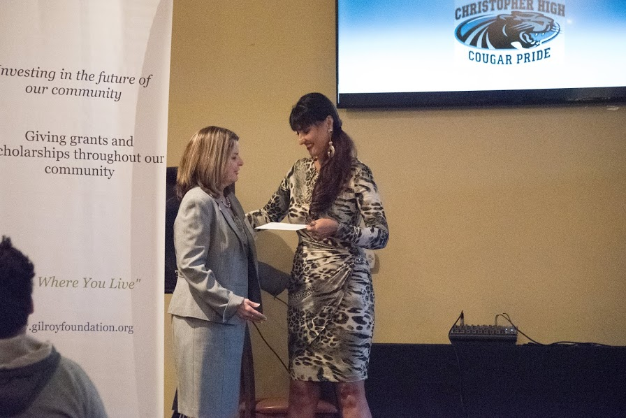 Photo of Karen La Corte handing a woman a grant award at the 2018 Annual Meeting and Charitable Giving Presentation