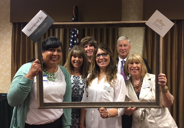 Photo of Yesenia Gonzalez, Marie Blankley, Vicky Campanella, Kurt Michielssen, and Donna Pray holding a large picture frame at 2017 Chamber Breakfast Sponsored by Pinnacle Bank