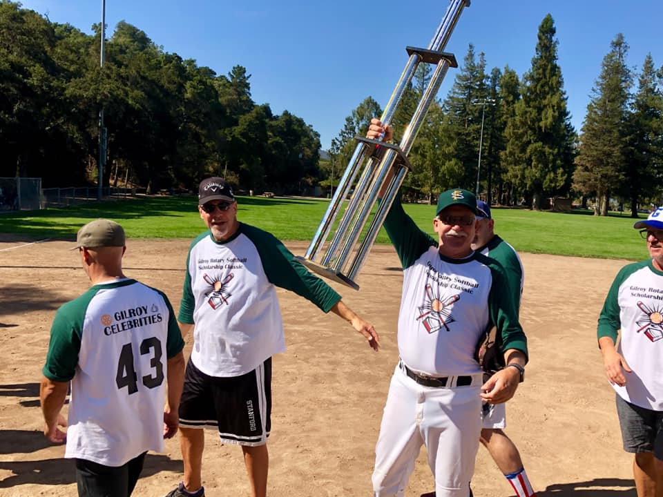 Photo of Joel Goldsmith holding up Celebrity Softball Game Trophy.
