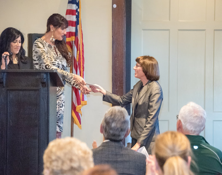 Photo of Karen La Corte handing a grant award to Dr. Deborah Flores, Superintendent of Gilroy Unified School District, at the 2018 Annual Meeting and Charitable Giving Presentation