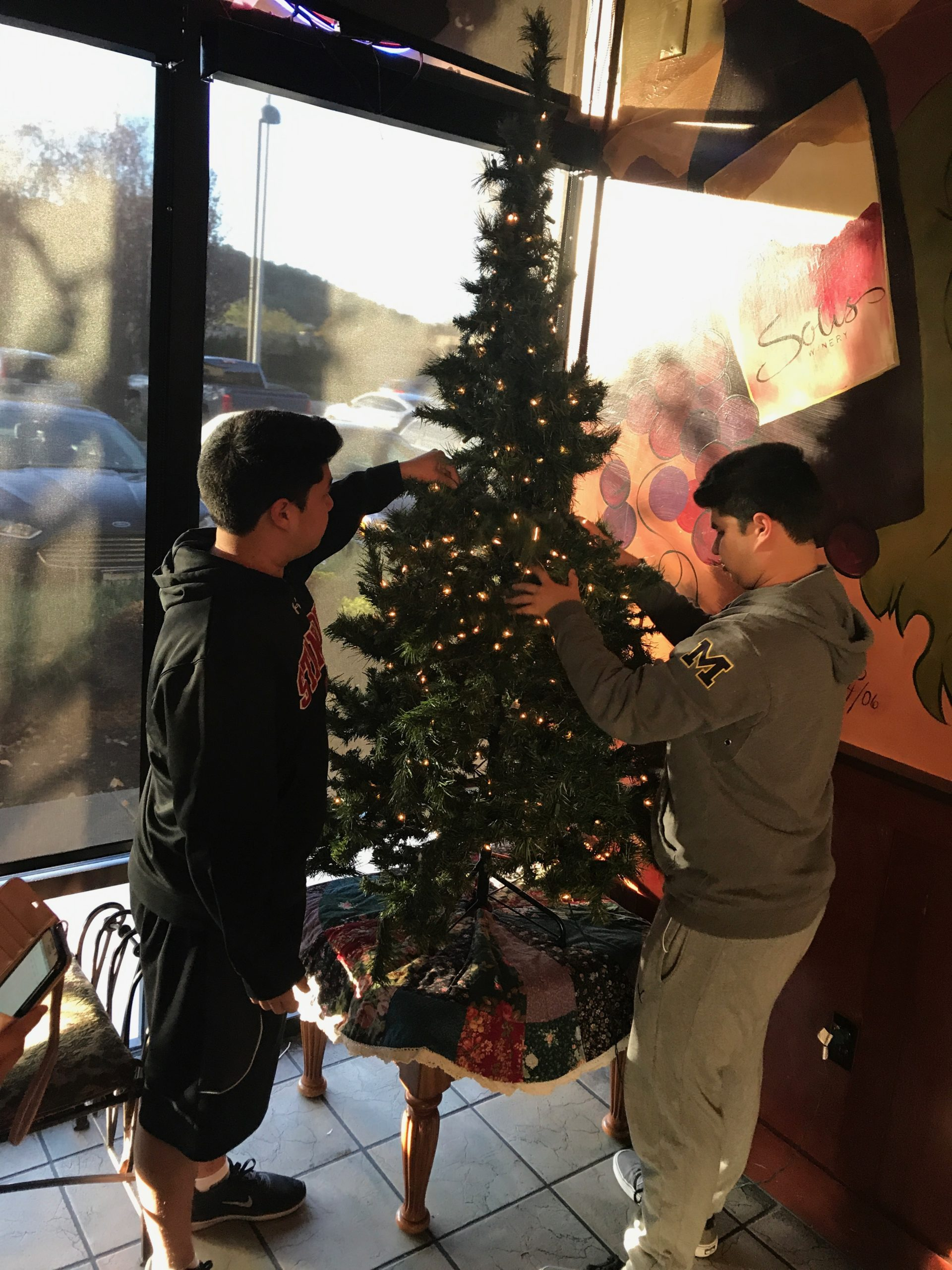 Photo of two boys putting ornaments and tags on a Christmas tree at West Side Grill
