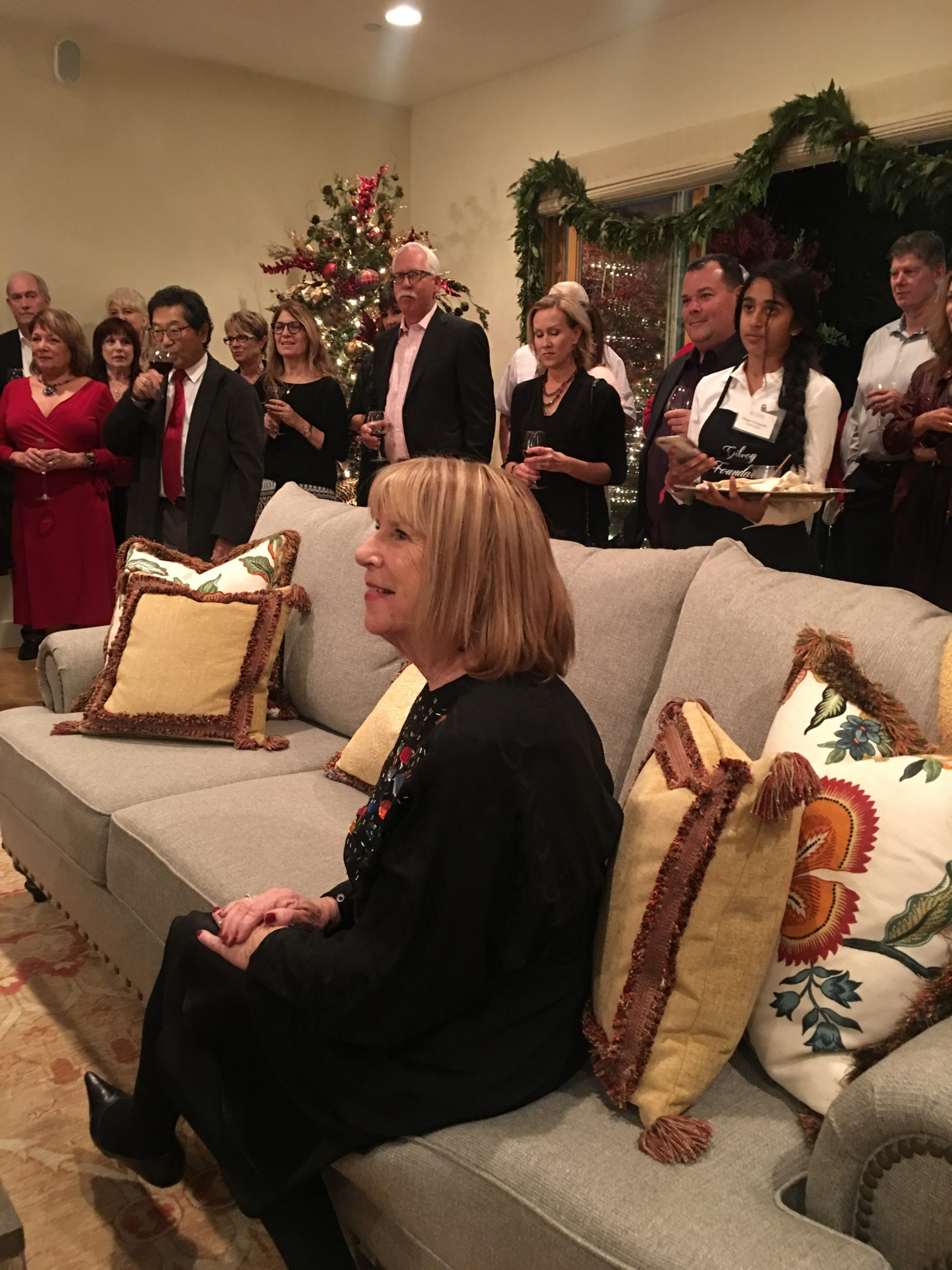 Photo of Donna Pray sitting on a couch at Gilroy Foundation's Holiday Party 2018