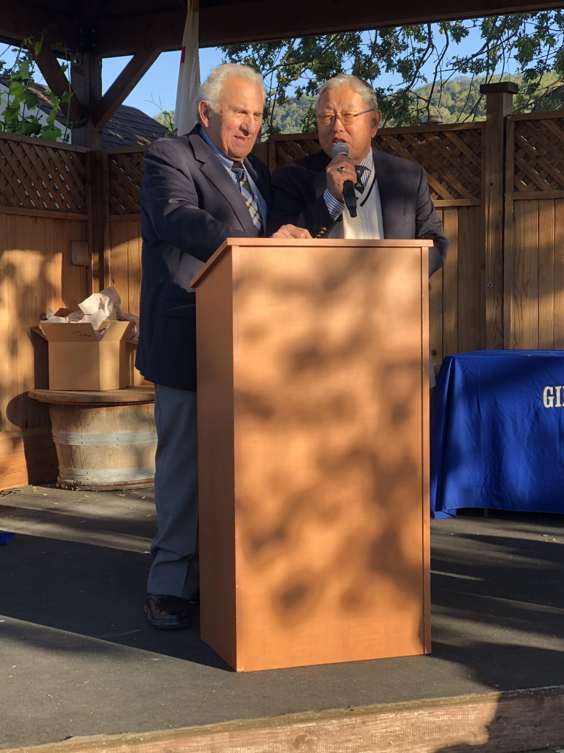 Photo of Sam Bozzo and Gene Sakahara standing at a podium at a scholarship award ceremony