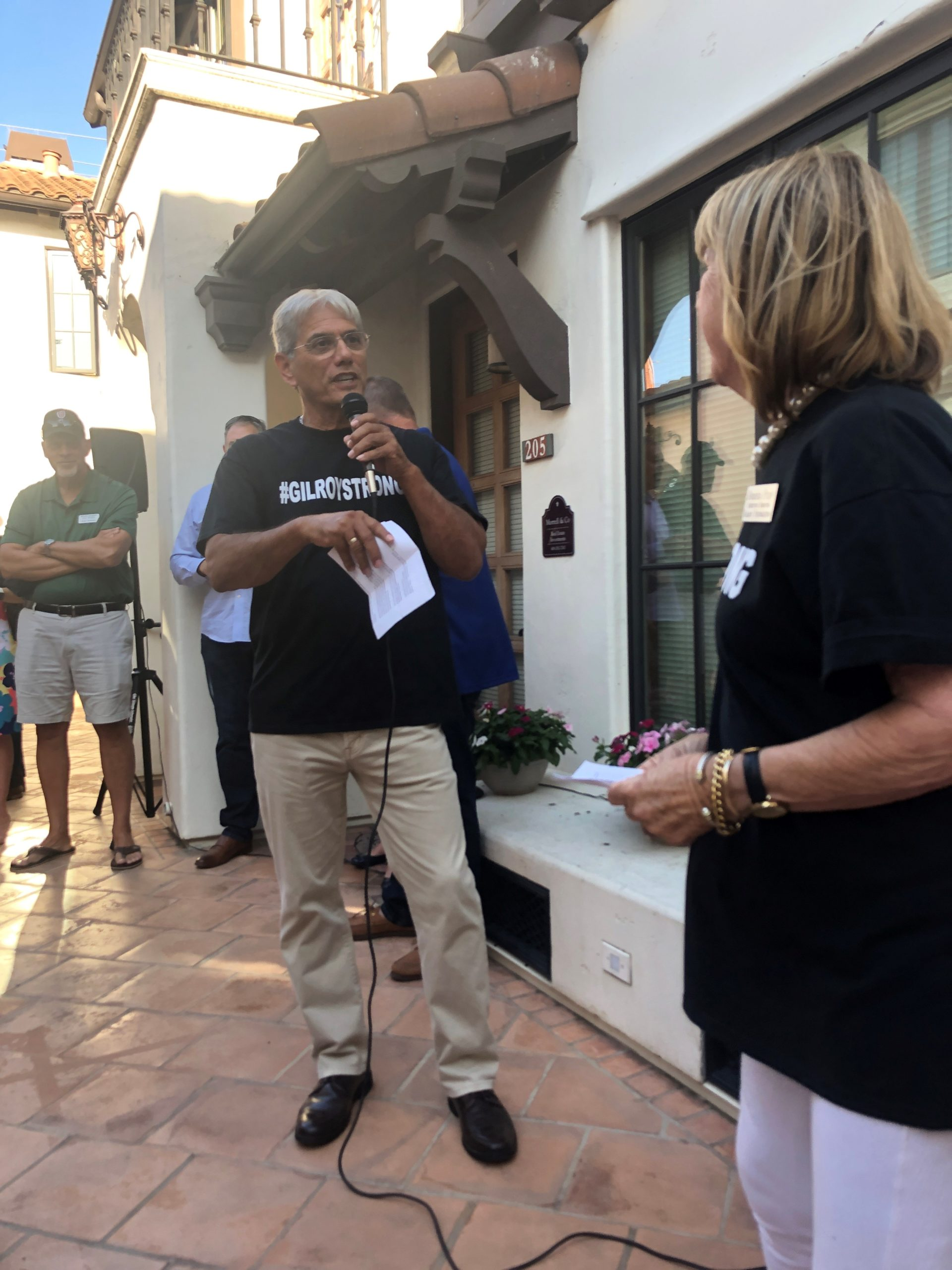 Photo of Edwin Diaz Speaking on the microphone to Donna Pray at Gilroy Foundation's Chamber Mixer