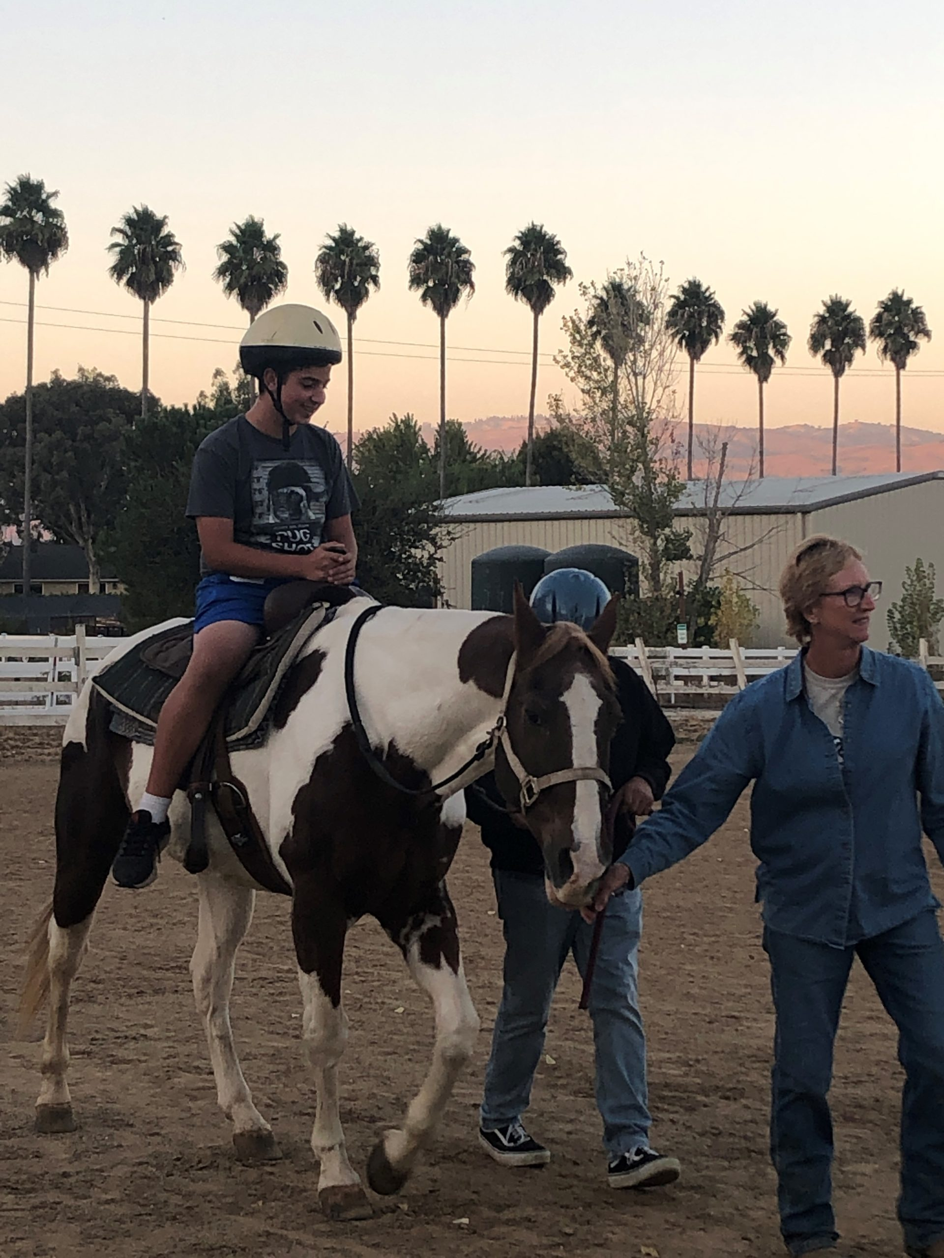 Photo of Gilroy Foundation Ambassador, Chris Wheeler guiding a Youth Board member on a horse