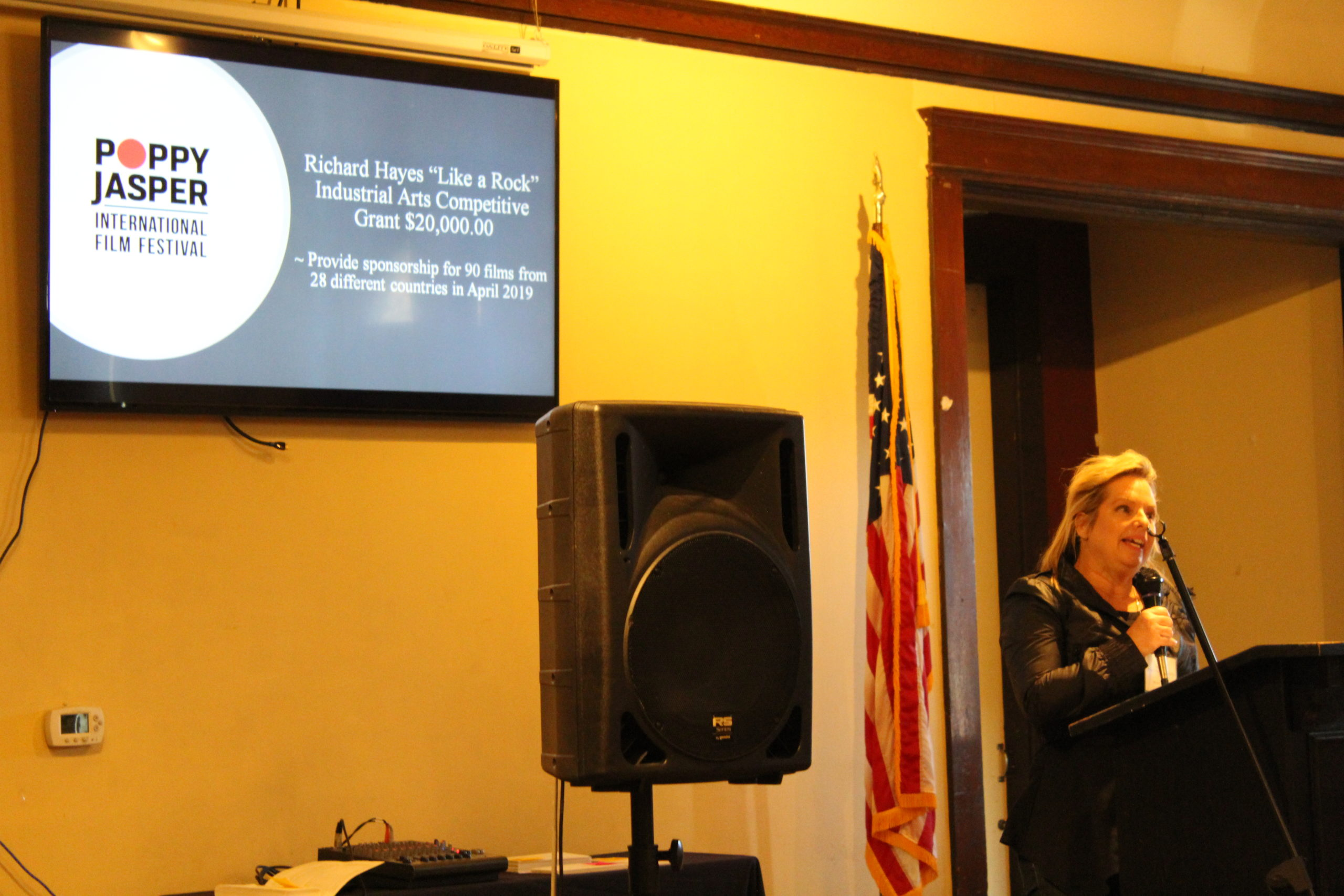 Photo of Mattie Scarriot, Executive Director or Poppy Jasper International Film Festival speaking into a microphone