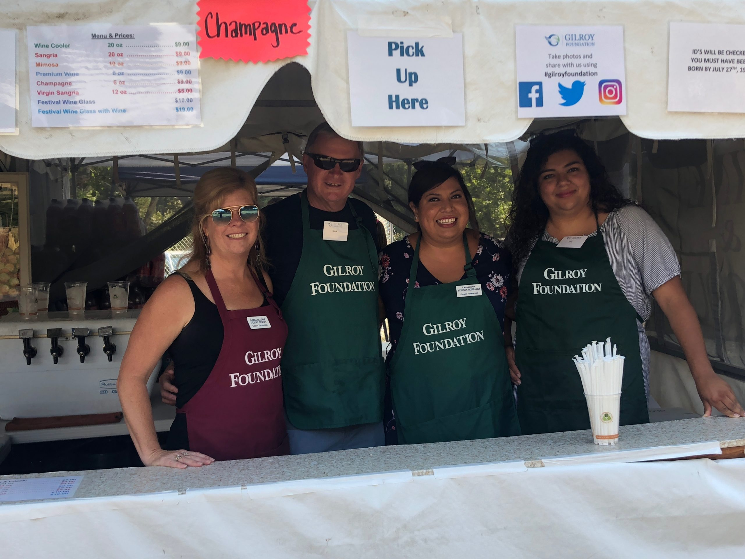Photo of Jenny Derry, Mark Derry, Yesenia Gonzalez, and Lily Becerra at Gilroy Foundation Garlic Festival Wine Booth