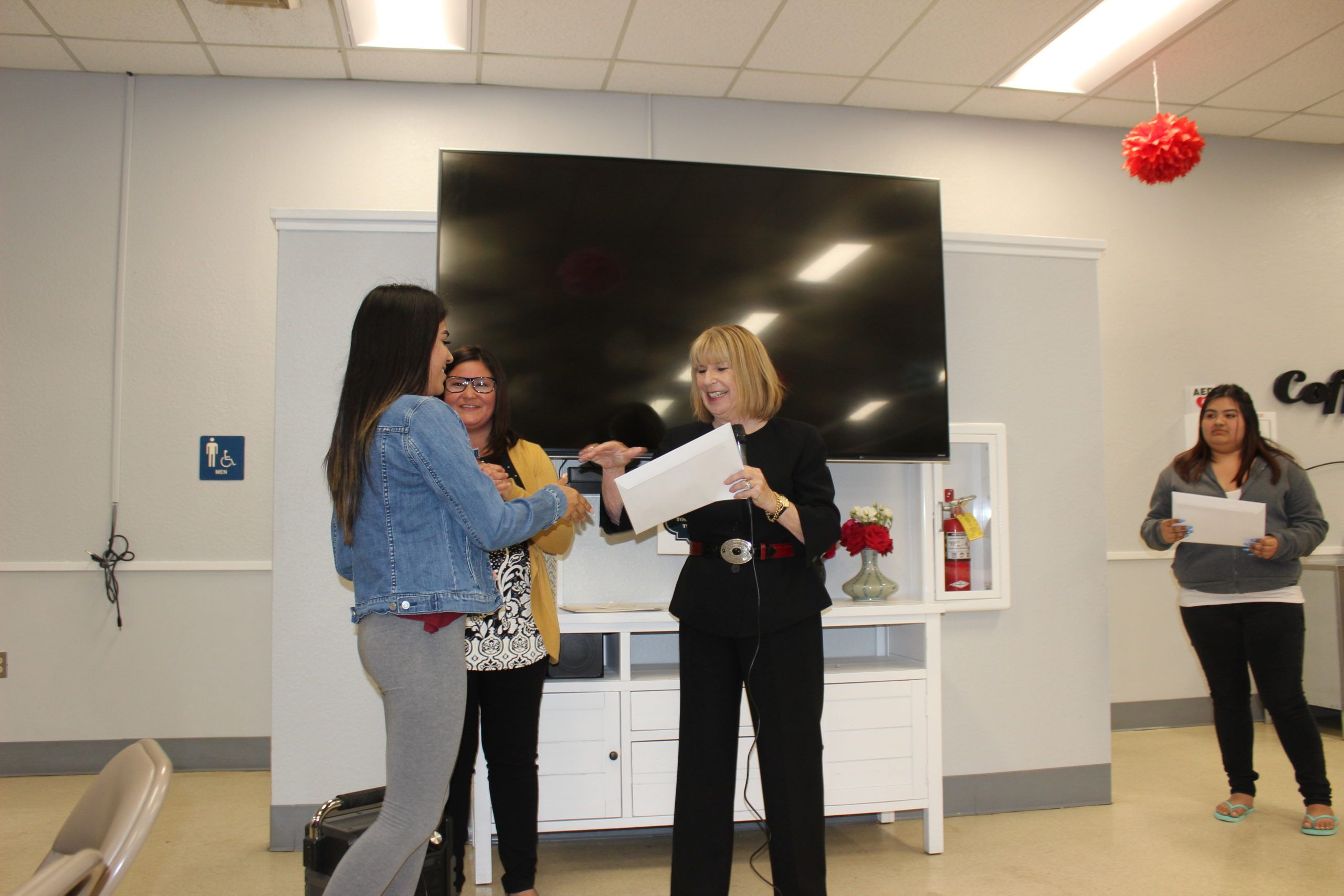 Photo of Donna Pray handing out a scholarship to a girl