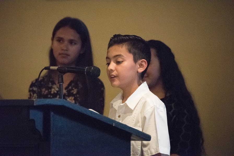 Photo of a Latino Family Fund Youth In Philanthropy Student speaking on microphone at the 2018 Annual Meeting and Charitable Giving Presentation