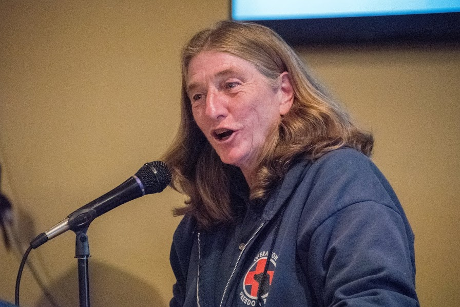 Photo of Mary Cortani, Executive Director of Operation Freedom Paws, speaking into a microphone at Gilroy Foundation's Annual Charitable Awards Ceremony