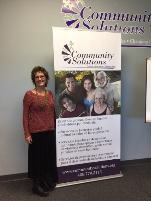 Photo of Lisa DeSilva stading with a Community Solutions Banner