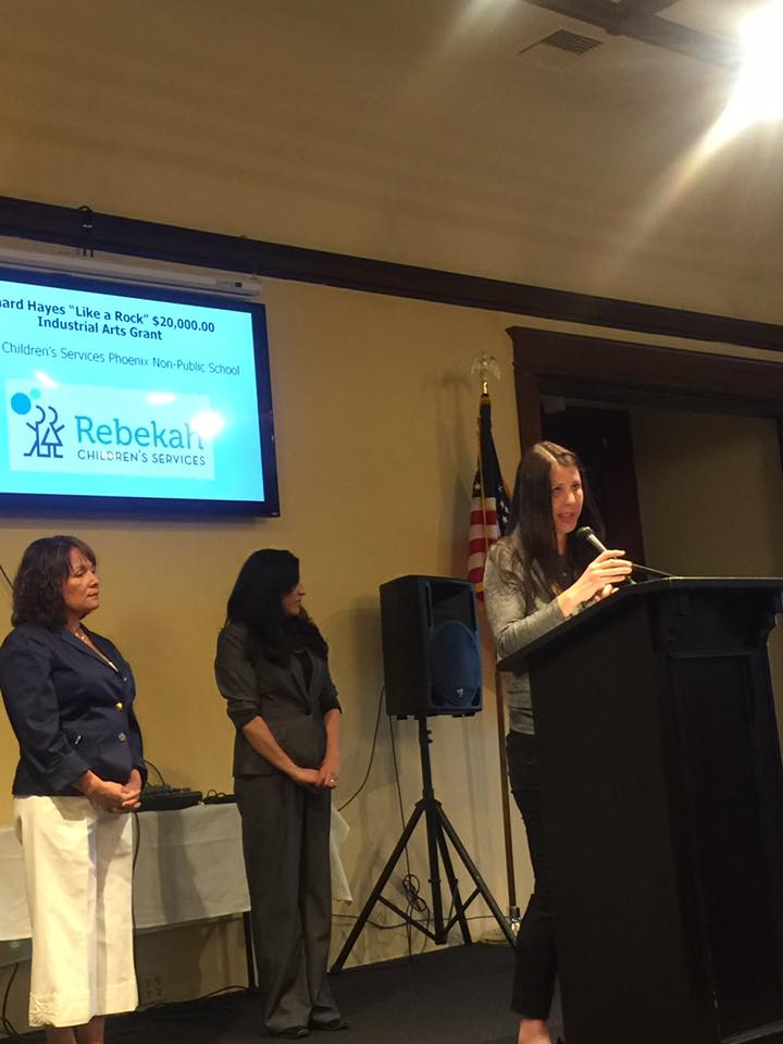 Photo of a grant recipient speaking into the microphone with Annie Tomasello and Lissa Gaffney standing behind her on stage at the 2017 Annual Meeting and Charitable Giving Presentation