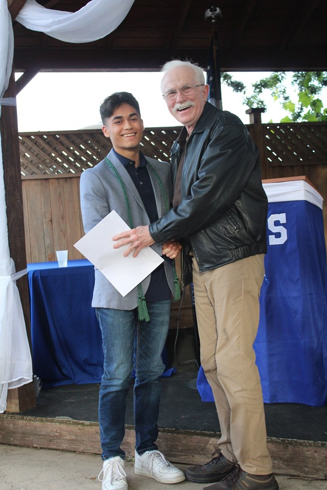 Photo of a man and a boy scholarship recipient